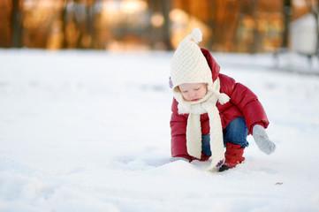 Toddler girl having fun on winter day