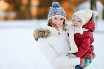 Young mother and her toddler daughter at winter