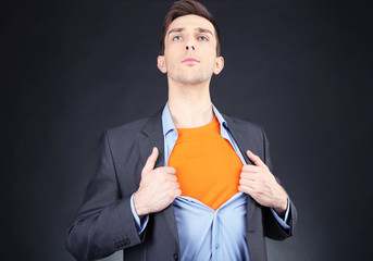Young business man tearing apart his shirt revealing  superhero