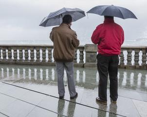Hombres con paraguas frente al mar