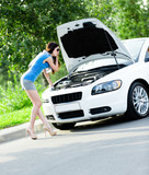Woman opens car hood and tries to repair the broken car