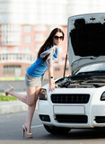 Woman repairing the broken car on the street