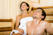 Half-naked man and female relaxing in sauna