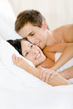 Man lying in bed-room with white linen embraces woman