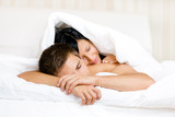 Woman sleeps on man in bed covered with blanket
