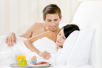 Lying man serves lady breakfast in bed