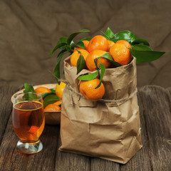Fresh tangerines in recycle paper bag and glass of juice on wood