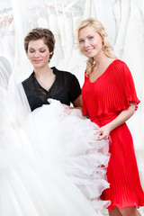 Two girls touch the wedding dress hesitating about fitting