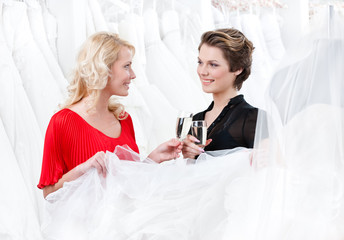 Two girls drink alcoholic drinks while discussing wedding gown