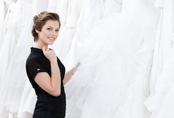 Shop assistant thinks about dress recommendation to the bride