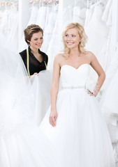 Professional designer and the bride examine the dress