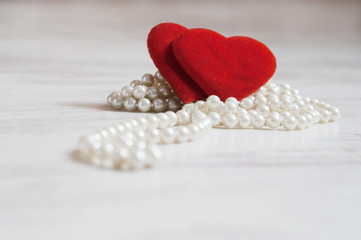 Two plush hearts on the pearls necklaces