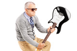 Angry mature man breaking an electric guitar