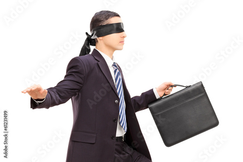 Blindfolded young businessman with briefcase