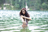 Young beautiful woman bathes in lake