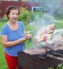 woman Cooking On A Barbeque in the garden