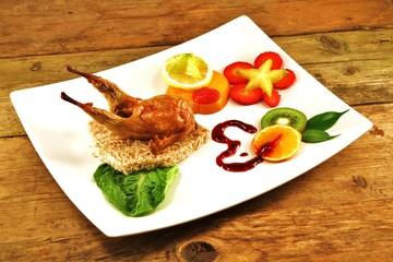 Südfrüchte in Scheiben und Wachtel auf Brot