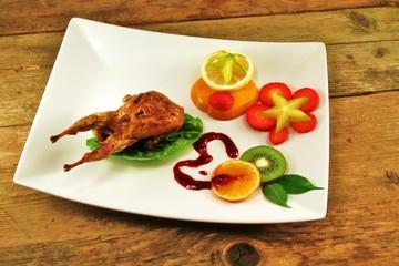 Südfrüchte in Scheiben und Wachtel auf Salatbett