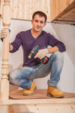 a young carpenter sitting and holding cordless drill