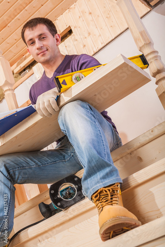 a young worker siiting on step of ladder and holding wooen board
