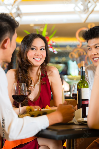 Waiter serving Chinese couple red wine in fancy restaurant