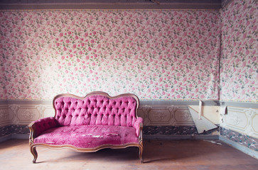 Old damaged red couch in an antique house. Flowers wallpaper