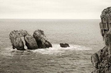 Rocks in te ocean water at sunset. Cantabria, Spain