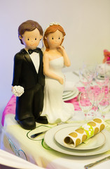 Figurines of bride and groom on a wedding table