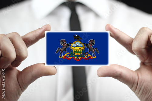 Businessman holding a business card with Pennsylvania State Flag