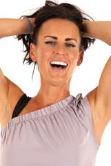 Female fitness model smiling pulling her hair back