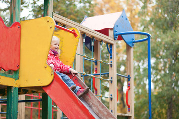 Little girl preparing to slither from a slide