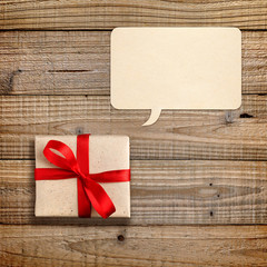 Gift box with red ribbon and speech bubble on wooden background
