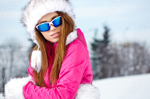 Happy young caucasian woman wearing ski goggles