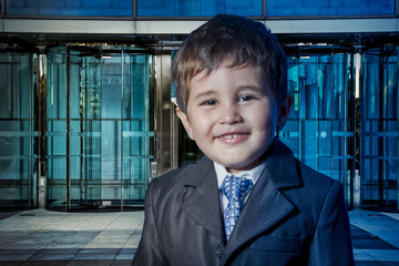 Happy child dressed businessman with hands in his tie and skyscr