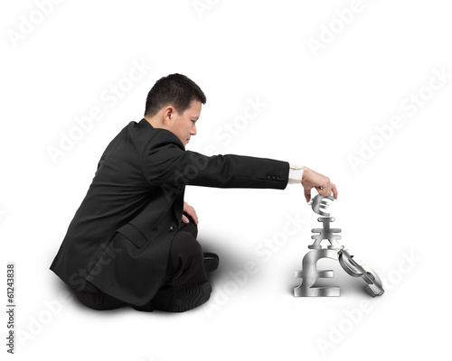 Businessman sitting and stacking 3D money symbols