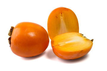 Persimmons, one whole and one cut in two pieces