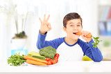 Boy eating carrot and gesturing happiness seated at table