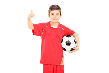Boy in sportswear holding a football and giving thumb up