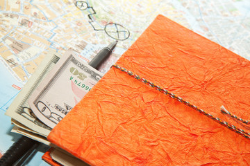 Close-up Travel Arrangement of Dollars , Map and notepad diary