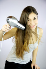 Happy young woman drying long hair