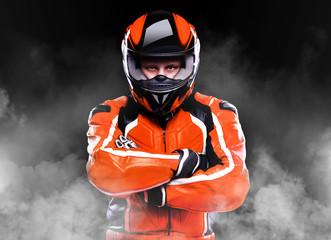 Motorcyclist standing in smoke on black background © iagodina