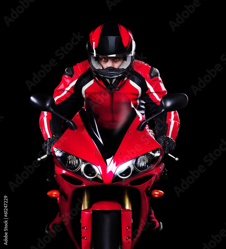 Motorcyclist in red equipment and helmet on black background