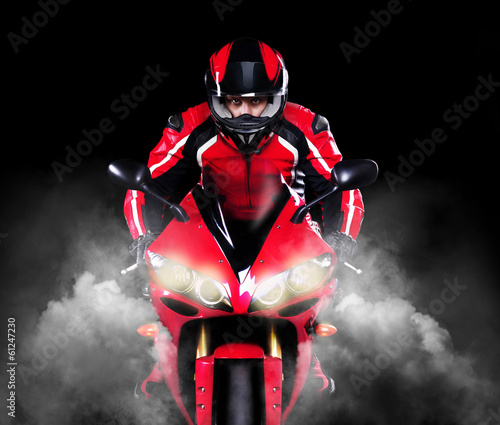 Motorcyclist riding motorbikeover black background