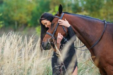Woman cuddling  horse head