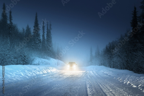 Car lights in winter Russian forest