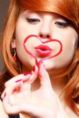 Redhaired girl holding valentine red heart love blowing kiss.