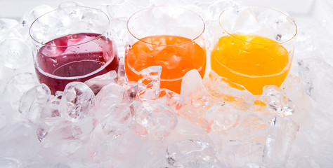 Mango, orange and grape fruit juices in short glass