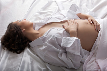 Portrait of sensual pregnant woman lying in bed