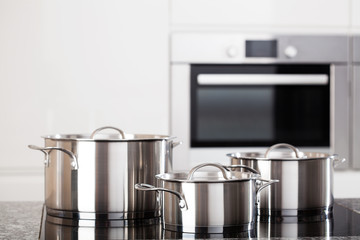 Three metal pots on induction hob