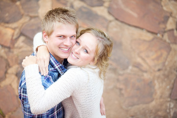 Young in-love adult couple smiling while hugging each other